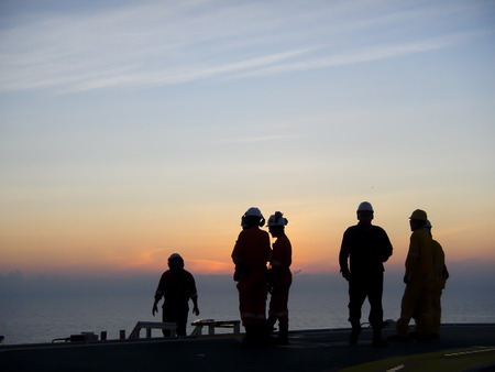 Oil and gas industry. Silhouette of offshore workers on helideck during sunset.