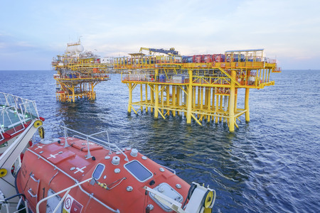 Oil and gas industry. View of commercial diving vessel nearby oil and gas drilling platform in open sea.