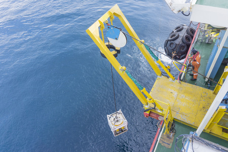Offshore worker standing on Remote Operated Vehicle (ROV) platform deploy ROV to the open sea.