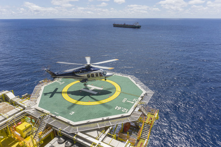 Oil and gas industry. A commercial helicopter landing on helideck at oil and gas platform in with backgroud open sea and tanker. Stok Fotoğraf - 95509428