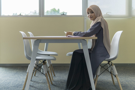 A beautiful Muslimah student with hijab sitting in the library and smiling.