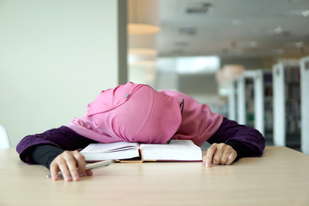 A beautiful Muslimah student holding a pen and sleeping on the book in the library.                     Фото со стока