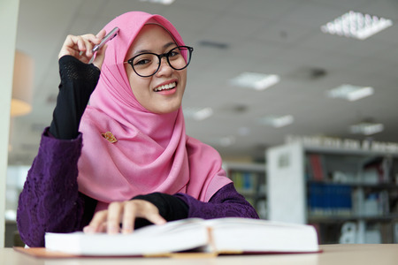 A beautiful Muslimah student holding a pen and smiling in the library