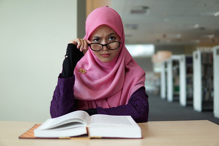 A beautiful Muslimah student sitting in the library with book open on the table, holding her glass and make facial expression.