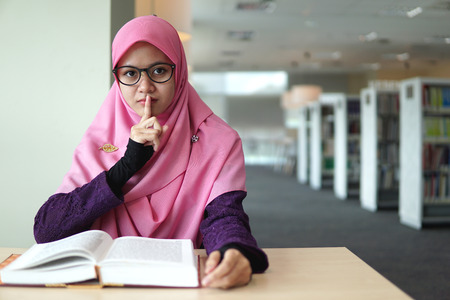 A beautiful Muslimah student sitting in the library with book open on the table, shows symbolic of keep quiet or shut up with facial expression.