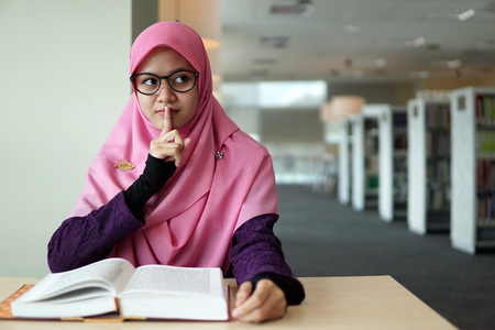 A beautiful Muslimah student sitting in the library with book open on the table, intervene somebody and shows symbolic of keep quiet or shut up with facial expression.