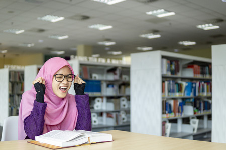 A beautiful Muslimah student sitting in the library with book open on the table shows exciting and happy facial expression.