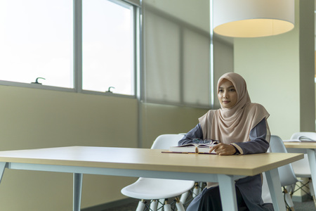 A beautiful Muslimah student sitting in the library and pensive thinking about something. Фото со стока