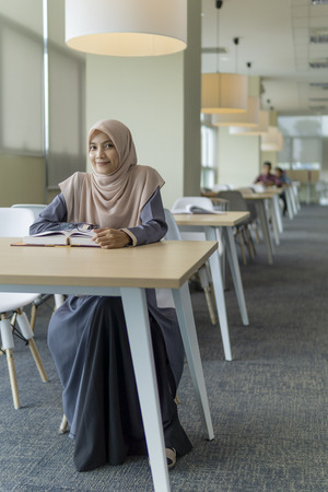 A beautiful Muslimah student sitting in the library and smiling. Фото со стока