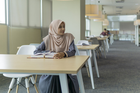 A beautiful Muslimah student sitting in the library and looking something at her left side. Фото со стока