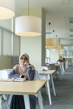 A beautiful Muslimah student with glass sitting in the library and smiling. Фото со стока