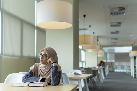 A beautiful Muslimah student sitting in the library with book open on the table and thinking with facial expression. Фото со стока