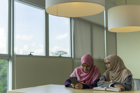 Two beautiful Muslimah students from Southeast Asian sitting in the library and looking to the mobile phone. Фото со стока