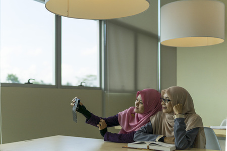 Two beautiful Muslimah students from Southeast Asian sitting in the library and selfie using a mobile phone.