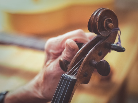 An old man luthier with aged hands is tuning a violin. You see other instruments like a guitar blurred in the background.