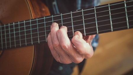 fretboard: An old man senior citizen luthier with aged hands is playing  grabbing a chord on a classical acoustic guitar. Close up of the fretboard and the fretting hand. Stock Photo