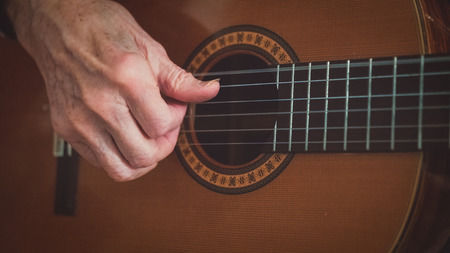 An old man senior citizen luthier with aged hands and guitar nails is playing a classical acoustic guitar. Close up of the right hand  fretting hand and the guitar body. Stock Photo