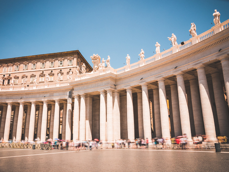 lining up: St. Peters square in the Vatican City within Rome, Italy during a sunny day in June. You see tourists lining up by the colonnades to get into the Basilica. Editorial
