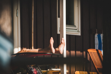after work: An old retired senior man is relaxing and sunbathing on the porch of his summer house. He is enjoying the quality of life after many years of hard work. Stock Photo