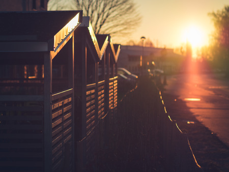 a wonderful world: A beautiful sunrise on a street in Lund, Sweden. The morning sun sunrays beautifully hit a couple of bicycle storage sheds. A wonderful world with backlight.