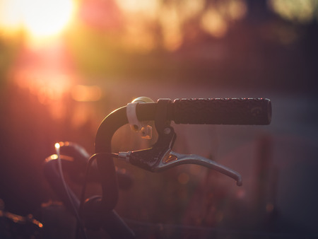 light  beam: The beautiful morning sun is shining on an old ladies grandma bicycle in Lund, Sweden. Vintage faded look. Close-up on the handlebar with the brake. Stock Photo