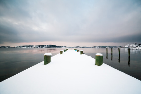 scandinavian landscape: A scenic Scandinavian Swedish winter landscape with a pier in southern Gothenburg, Sweden covered in snow in December.
