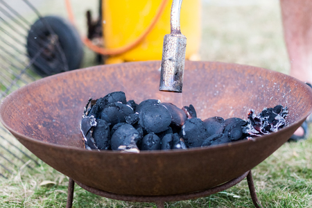 An old-fashioned charcoal grill is being lit by gas before a barbeque dinner. Location: Denmark.