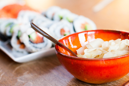 ginger health: A big bowl with ginger gari and many rolls of maki California rolls in the background.