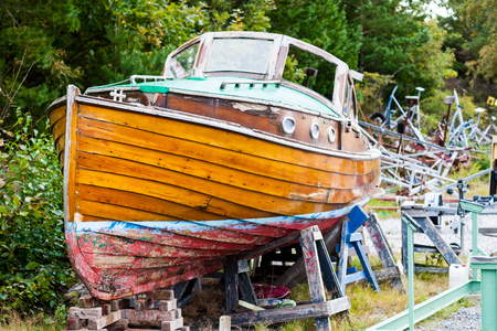 sail boat: A beautiful old wooden boat is up on land for repairs in a dry dock. Location: Sweden. Stock Photo