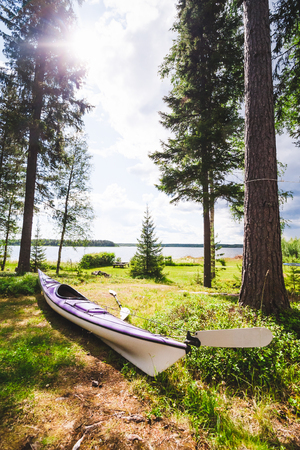 sweden resting: A purple sea kayak touring kayak is lying in the grass close to the ocean in a beautiful Scandinavian forest setting. Location: Northern Sweden. Stock Photo