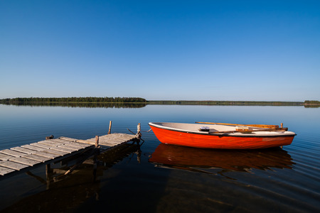jetty: A beautiful idyllic view of a glassy lake in northern Sweden. The sky is perfectly blue and you see a rowing boat with fishing gear docked by a small jetty.