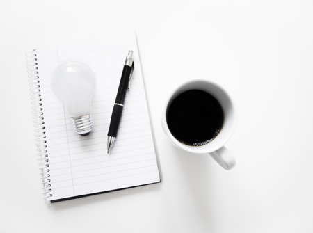 A fresh cup of coffee stands next to a notepad with a pen and a lightbulb on top. All on a bright white table. New idea concept.