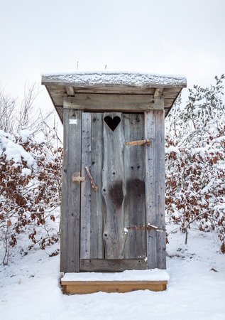 latrine: A wooden outhouse or privy in the Swedish winter, surrounded by snow. It has a heart on the door. Location: Amundon, Gothenburg, Sweden.