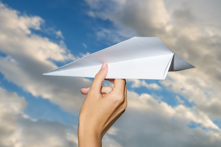 Hand Throwing A Paper Plane On Sky photo