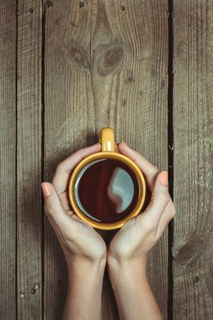 copa: Manos femeninas que sostiene la taza de café