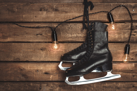 Old Black Figure Ice Skates Hanging On A Wooden Wall