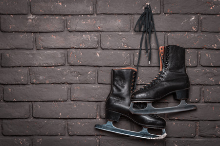 winterday: Old Black Figure Ice Skates Hanging On A Brick Wall Stock Photo