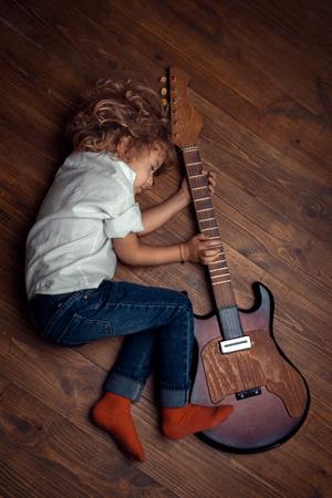 barefoot people: Little Boy Sleeping And Hugging Guitar