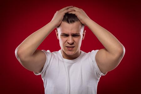 Stattlicher Mann, der seinen Kopf auf rotem Hintergrund