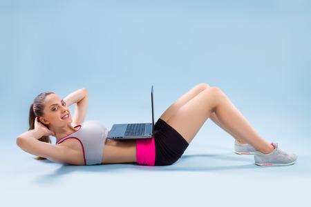 ejercicio: Mujer de la aptitud que hace ejercicios con ordenador portátil