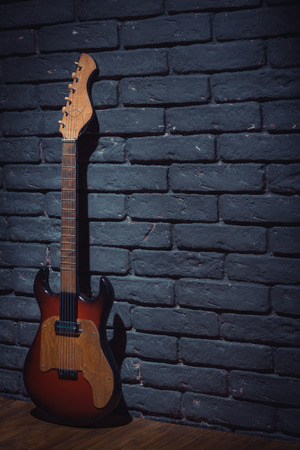 writing western: Electric Guitar Leaning On Brick Wall