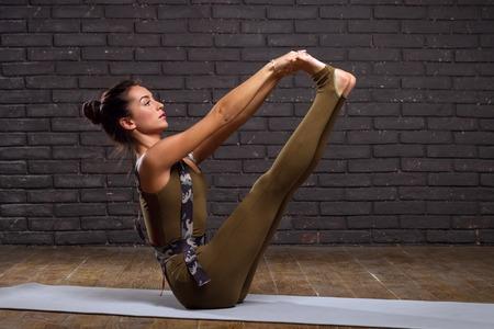 sports clothing: Beautiful Girl Doing Yoga Exercises On Brick Wall Background