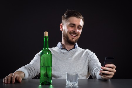 drinking drunk: Drunk Man With Bottle Holding Mobile And Going To Make A Call On Black Background