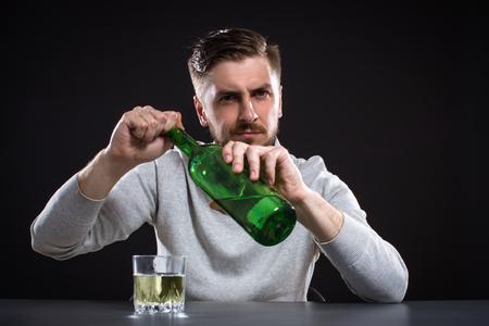 borracho: Hombre frustrado Abre Una Botella En Fondo Negro Foto de archivo