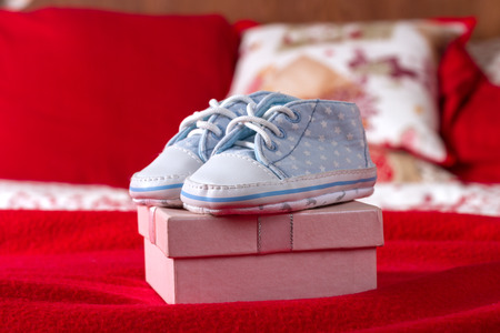 red bed: Blue Baby Shoes On Pink Gift Box In Red Bed Stock Photo