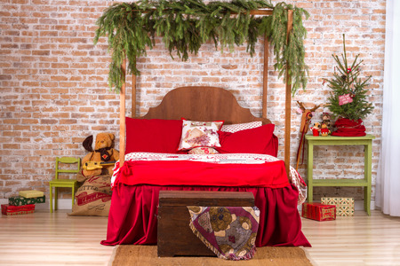 bed clothes: Red Bed In Christmas Interior On Brick Wall Background