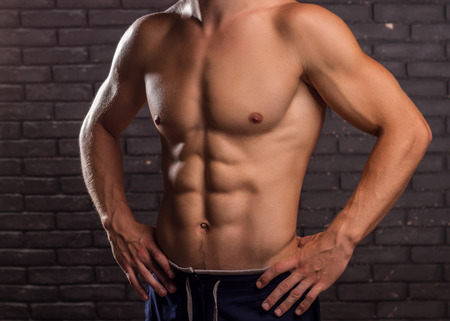 abdominal wall: Muscular Handsome Man Demonstrates His Abdominal Muscles On Brick Wall Background