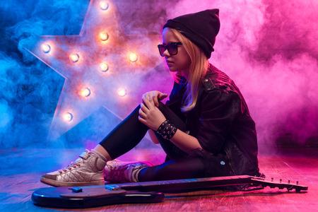 ni�as peque�as: Ni�a Estrella del rock con la guitarra el�ctrica se sienta en el suelo en el fondo de humo Foto de archivo
