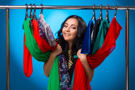 clothing: Happy Woman At The Clothing Rack With Dresses On Blue Background