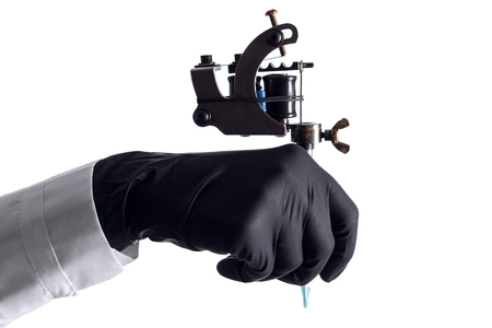Hand In Black  Nitrile Glove Holding Tattoo Machine On White Background Imagens